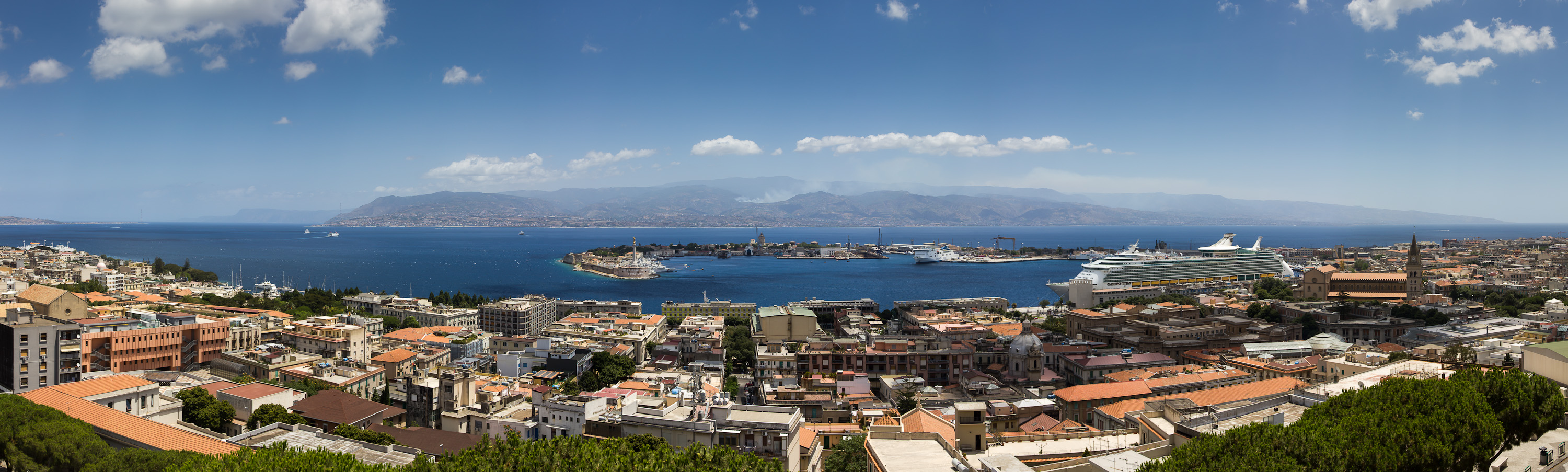 Messina Strait seen from Messina towards the Italian Mainland Panorama 1/320sec at f/8 ISO 100 EF-S 15-85 f3.5-5.6 IS USM at 28mm The Strait of Messina (Stretto di Messina in Italian, Strittu di Missina in Sicilian) is the narrow passage between the eastern tip of Sicily and the southern tip of Calabria in the south of Italy. It connects the Tyrrhenian Sea with the Ionian Sea, within the central Mediterranean. At its narrowest point, it measures 3.1 km (1.9 mi) in width, though near the town of Messina the width is some 5.1 km (3.2 mi) and maximum depth is 250 m (830 ft). A ferry service connects Messina on Sicily with the mainland at Villa San Giovanni, which lies several kilometers north of the large city of Reggio Calabria; the ferries hold the cars (carriages) of the mainline train service between Palermo and Naples. There is also a hydrofoil service between Messina and Reggio Calabria. The strait is characterized by strong tidal currents, that established a unique marine ecosystem. A natural whirlpool in the Northern portion of the strait has been linked to the Greek legend of Scylla and Charybdis. In some circumstances, the mirage of Fata Morgana can be observed when looking at Sicily from Calabria (Wikipedia)
